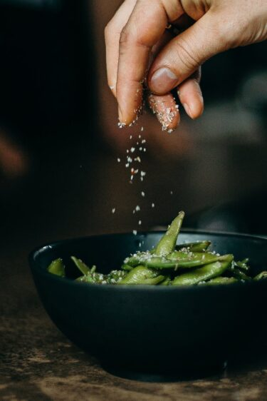 person pouring seasoning on green beans on bowl